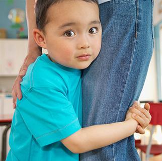 Preschool boy holding on to his moms leg.