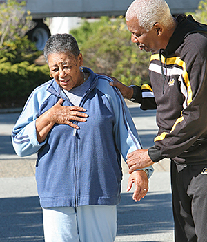 Senior African-American woman in pain with hand on chest.
