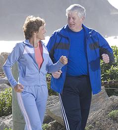 Man and woman walking along beach.