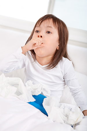 Sick little girl coughing in bed.