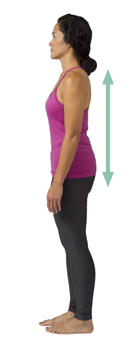 Side view of woman standing with ears, shoulders, hips, and ankles aligned.