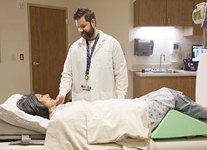 Technician preparing woman for x-ray.
