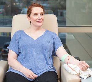 Technician taking blood donation from man's arm.
