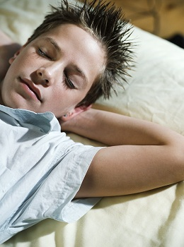 Teen boy lying on bed with his eyes closed