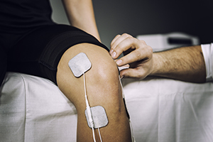 TENS electrodes positioned to treat knee pain in physical therapy