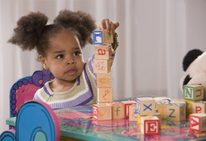 Toddler girl playing with play blocks.