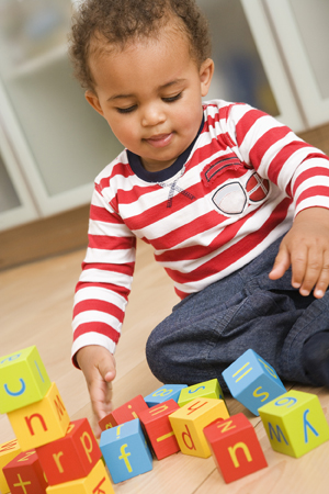 Toddler sitting on floor playing with blocks.