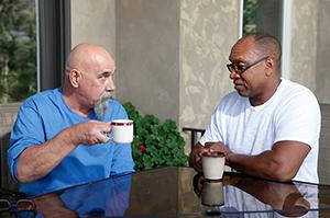 Two men sitting outdoors, talking.