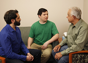 Two men talking to mental health professional.