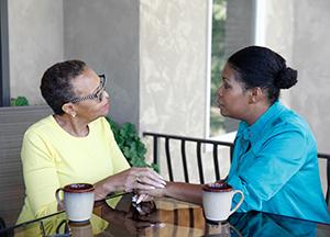 Two women sitting outdoors talking.