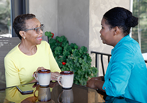 Two women talking together over coffee.