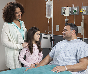 Woman and girl visiting man in hospital bed.