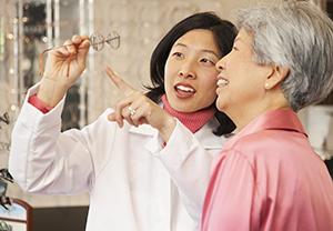 Woman and man looking at glasses at optician's.