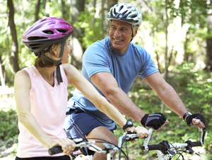 Woman and man on mountain bikes, wearing helmets.