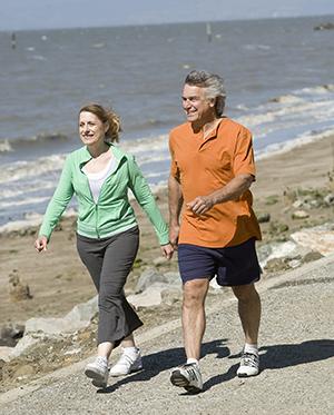 Woman and man walking at beach.