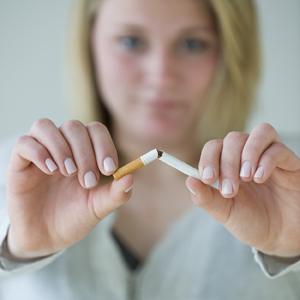 Woman breaking cigarette.