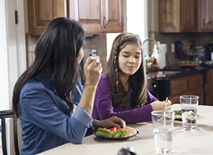 Woman bringing teen girl water and healthy snack in kitchen.