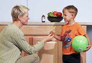 Woman handing liquid medicine to boy.