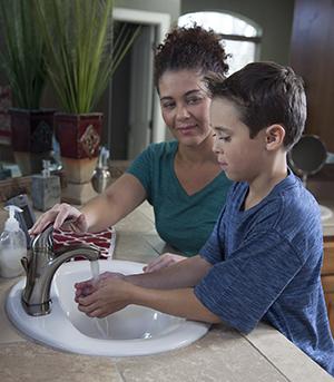 Woman helping boy wash hands at bathroom sink.