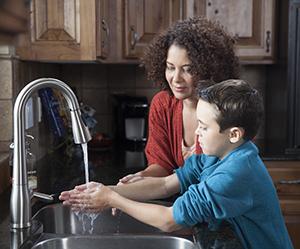 Woman helping boy wash hands in kitchen sink.