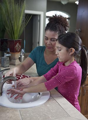 Woman helping girl wash hands in bathroom.