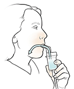 Woman inhaling medication from nebulizer with mouthpiece.