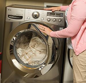 Woman loading sheets into home washing machine.