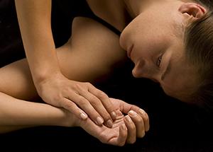 Woman lying on floor in dark room.