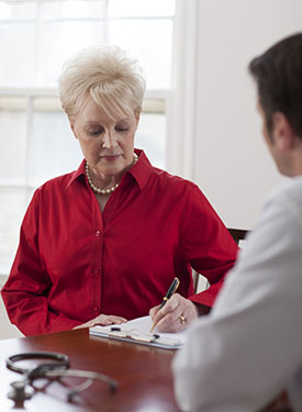 Woman meeting with a doctor. She is writing information on a pad of paper.
