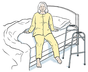 Woman preparing to lie down in bed. Walker by bed.
