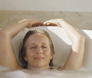 Woman relaxing in bathtub.