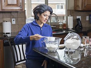 Woman sitting at kitchen counter, measuring baking ingredients.