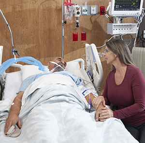 Woman sitting next to bed of intubated man in intensive care unit.