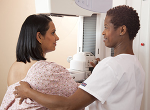 Woman standing next to mammography machine. Health care provider is positioning woman's breast on machine.