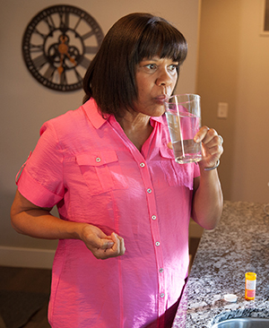 Woman talking a pill and holding a glass of water.