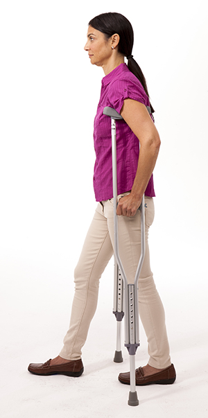 Woman walking with crutches.