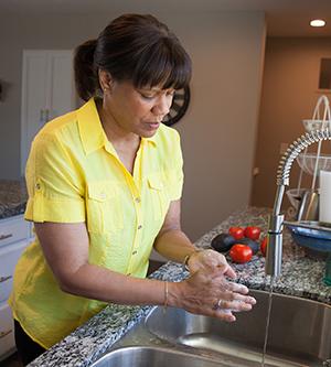 Woman washing hands at kitchen sink.