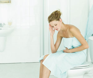 Woman wrapped in a towel, sitting on a closed toilet, holding her belly and head.