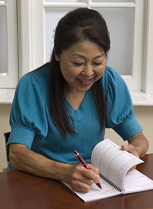 Woman writing in calendar.