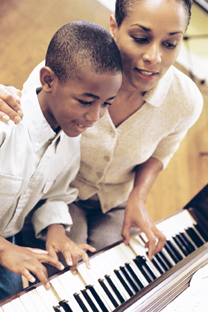 Young boy and woman playing a piano together.