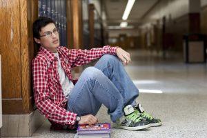 Young man sitting against a wall in school hallway