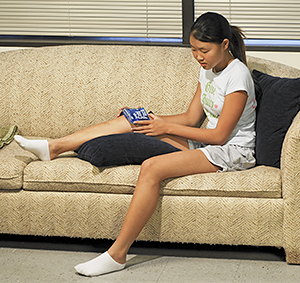 Young teenage girl sitting on couch with ice pack over her knee.