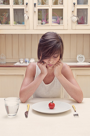 Young woman starting at small tomato on her plate.