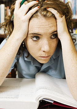 Young woman studying and looking stressed. She's holding her head and hair in her hands.