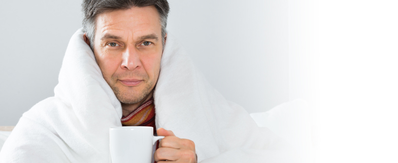 Man in bed, wrapped in blankets with a cup of tea in hand.
