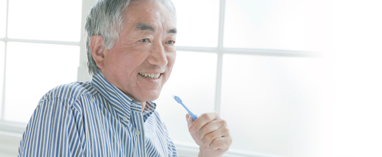 Man of senior age with a toothbrush in his hand