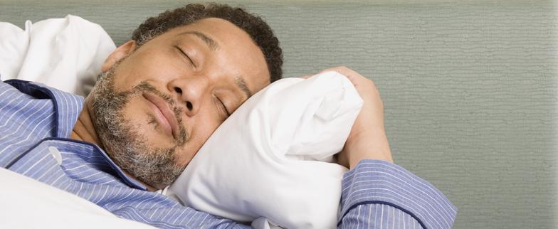 Older African American male sleeping peacefully in bed