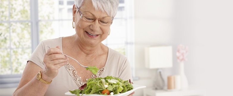 Older woman eating a heart healthy salad.