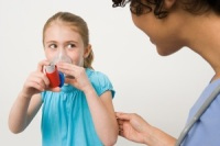 Photo of young girl using asthma inhaler while mother watches