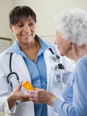 A doctor handing a patient medication bottle.